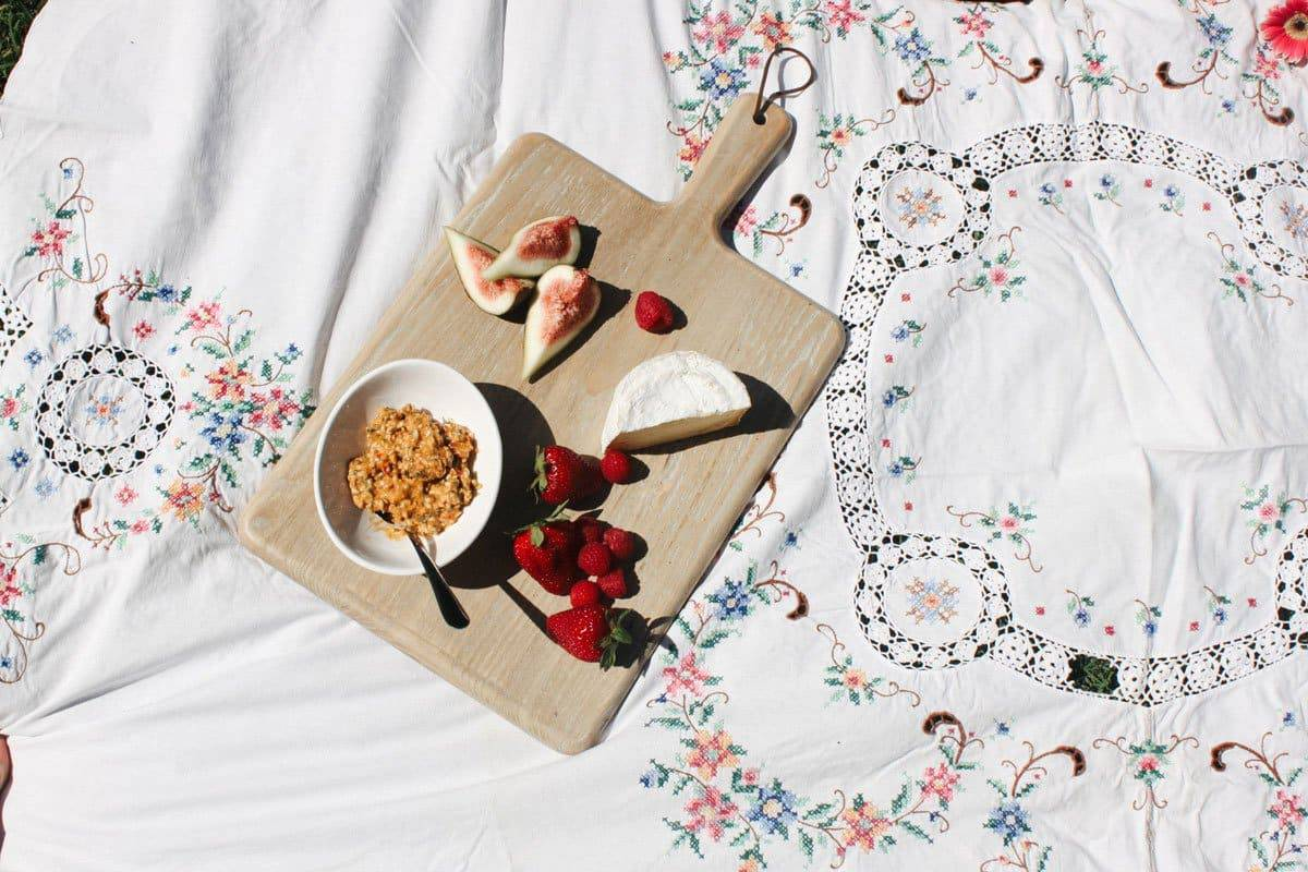 Cheese board with strawberries on pretty floral and lace cloth.