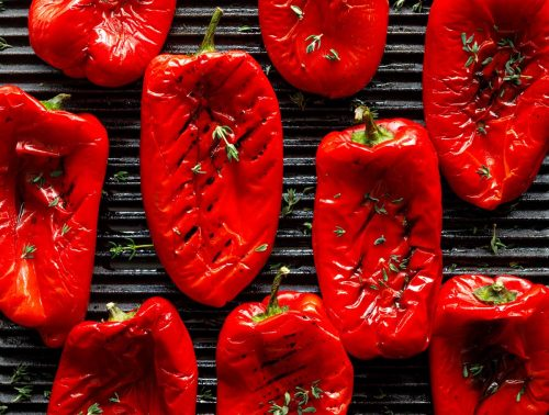 Red peppers grilling on a griddle pan with char marks.