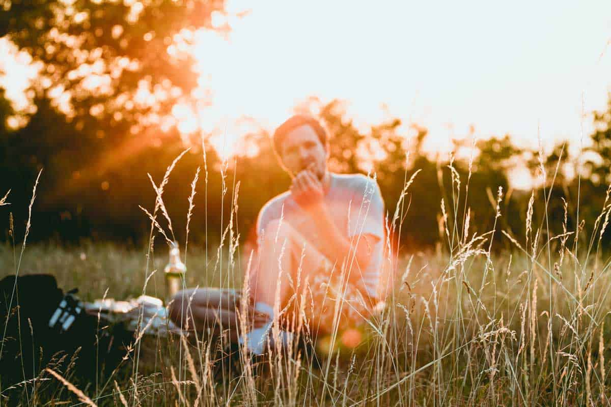 Man enjoying a picnic in a field in the fading sun.