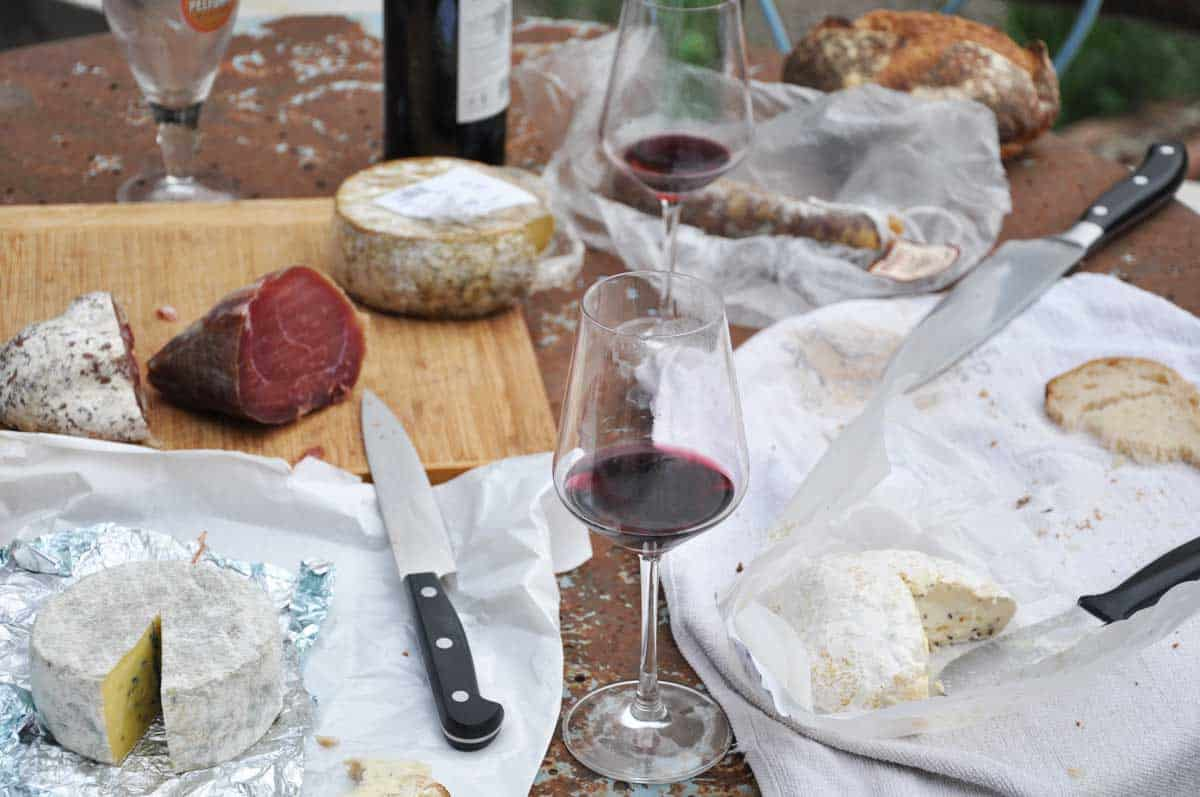 Glasses of red wine and assorted cheeses laid out on a table.
