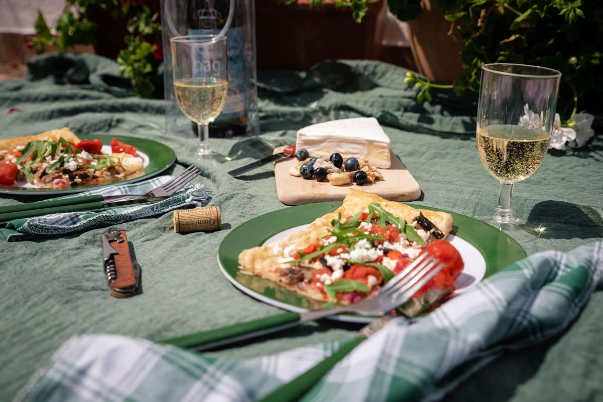 Picnic scene with food and wine laid on the blanket.