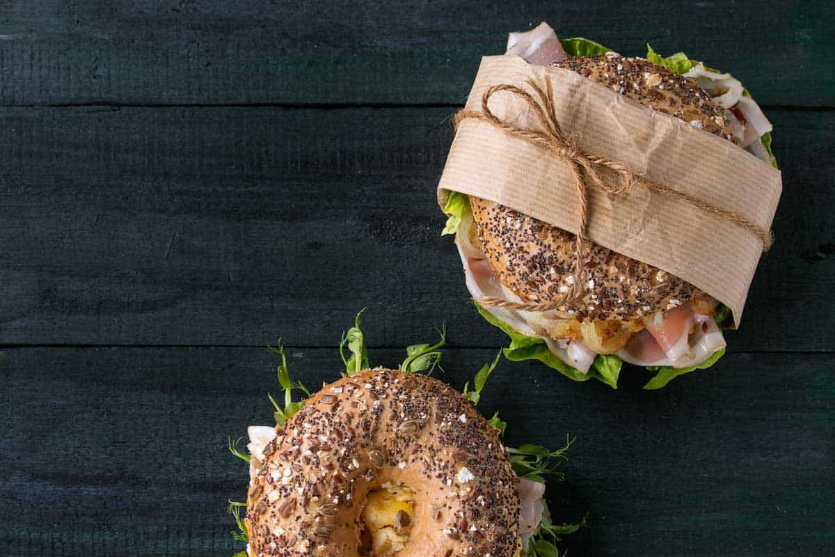 Overview of seeded bagels wrapped in brown paper tied with string.