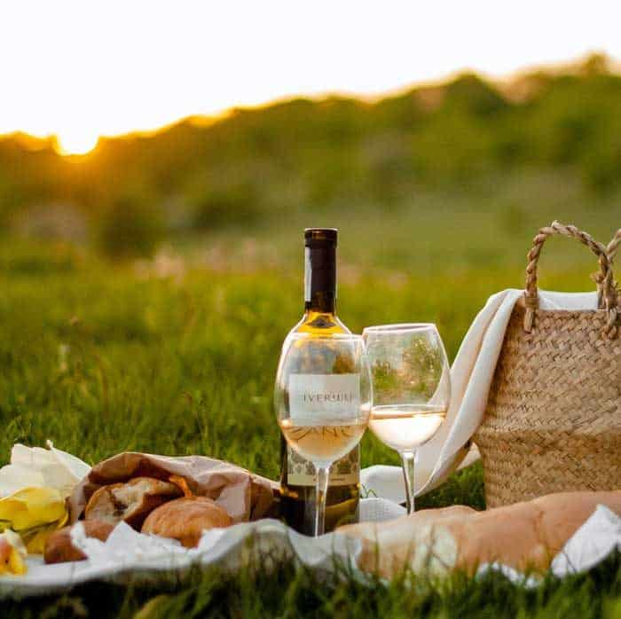 Picnic scene with wine glasses and basket in a field.