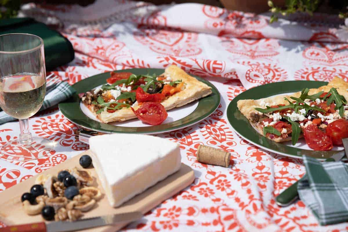 Brightly patterned picnic blanket laid with cheese platter, glass of wine and vegetable tarts.