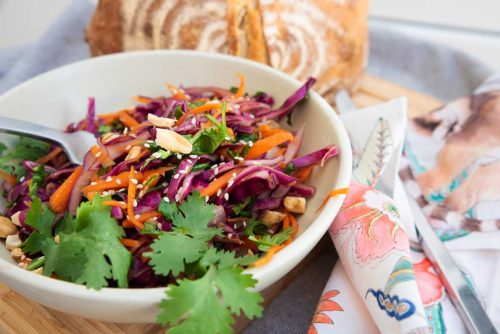 Asian coleslaw with fresh bread at a picnic.