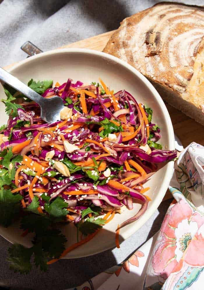 Bowl of brightly coloured Asian coleslaw with loaf of fresh bread.