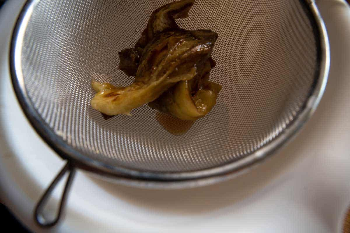 Pieces of roasted eggplant flesh draining in a sieve.