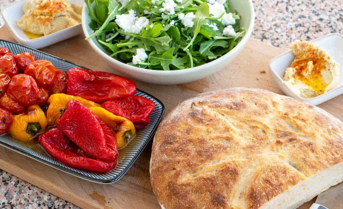 Roasted peppers with homemade bread, green salad and hummus on a wooden board.