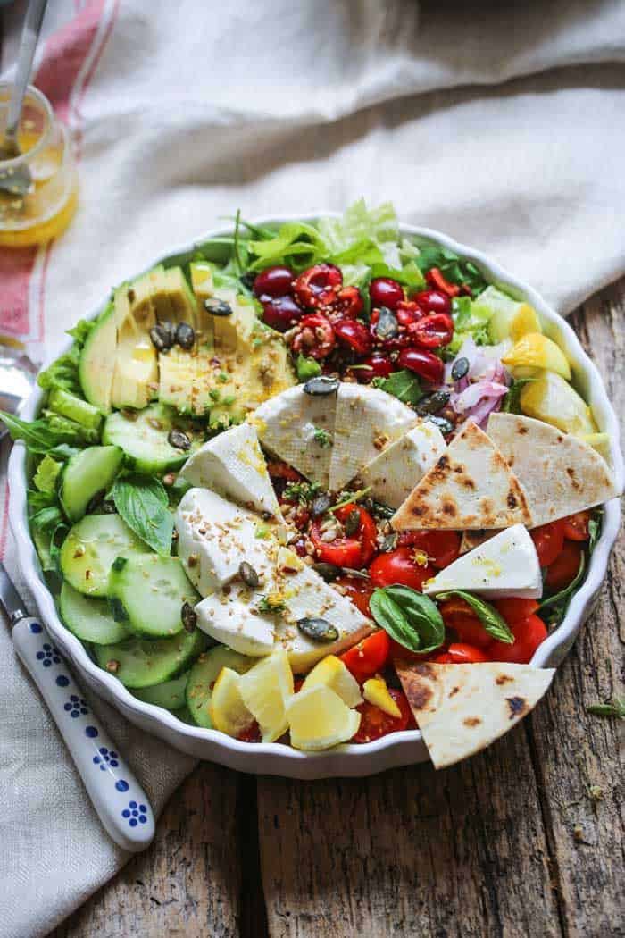Brightly coloured salad with wedges of cheese.