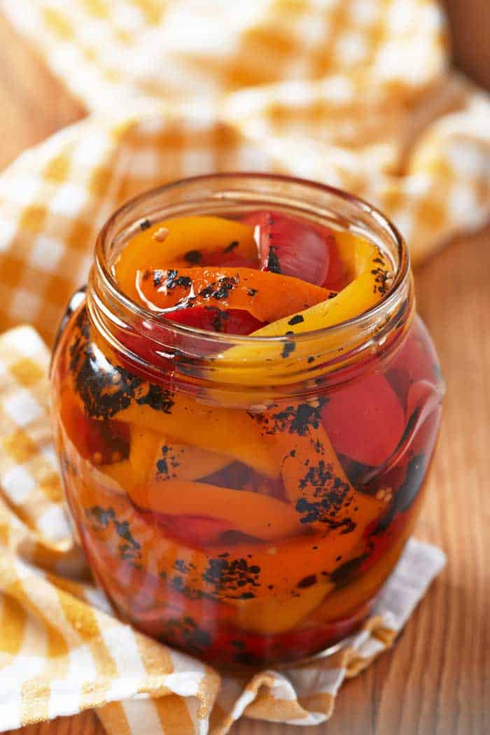 Jar with strips of roasted pepper in oil.