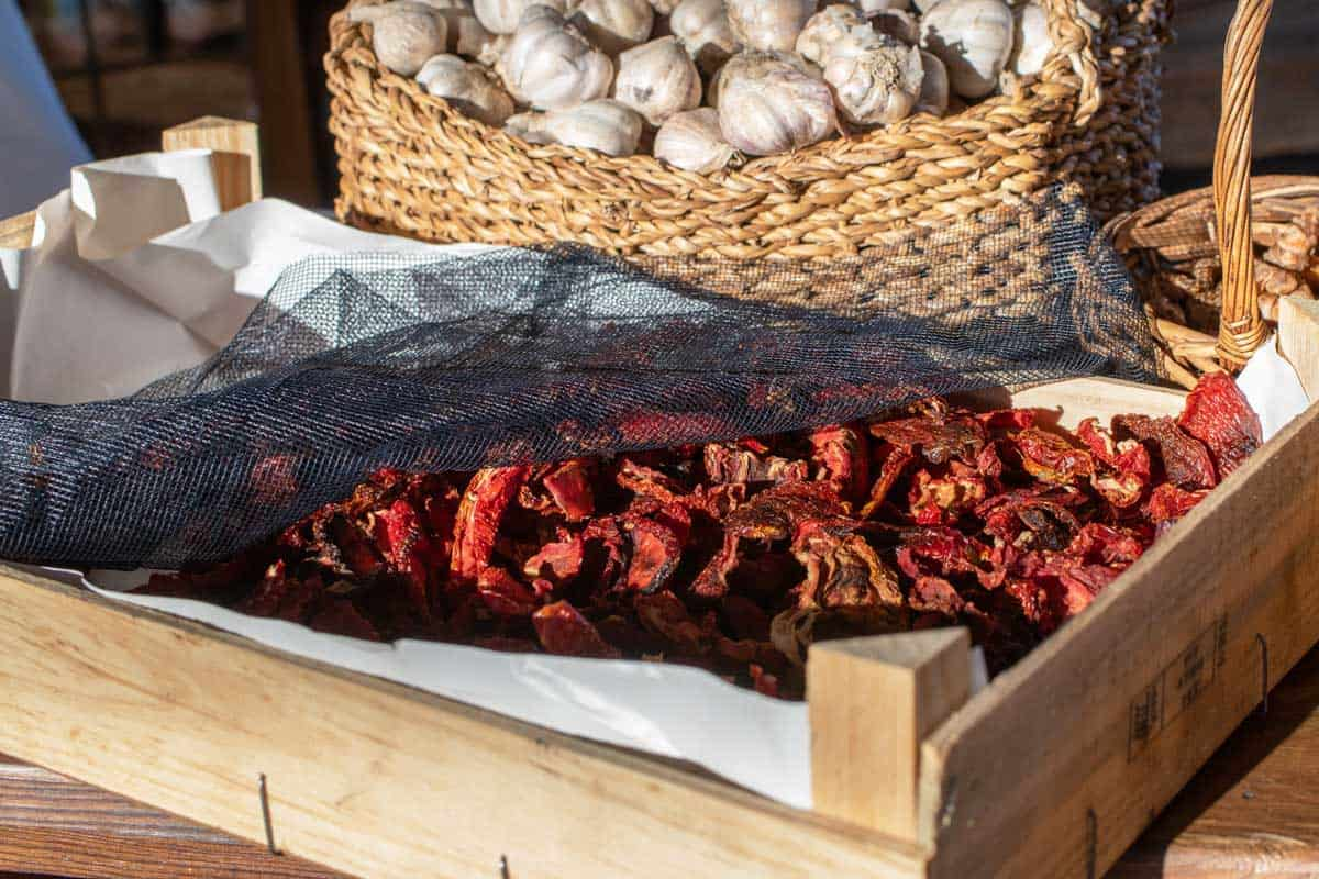 Wooden box with sun dried tomatoes and baskets of fresh garlic in the background.