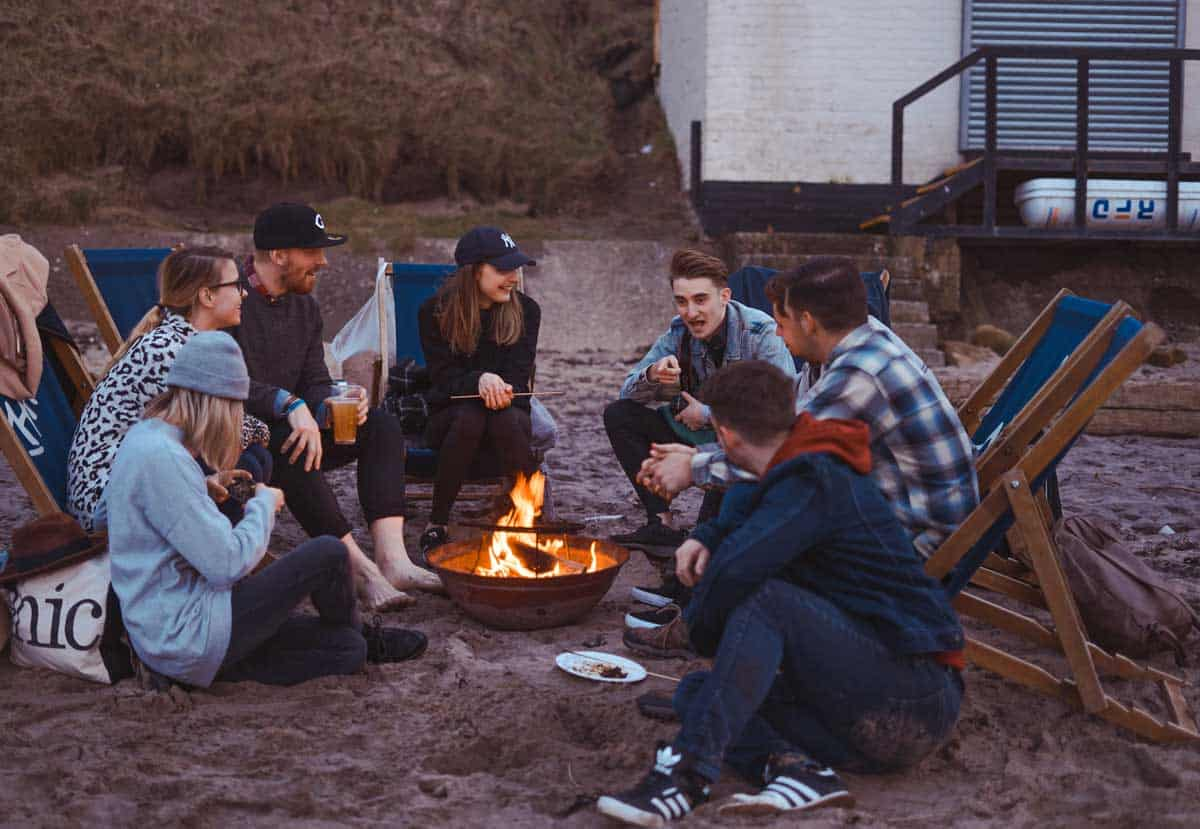 Group of friends around a bonfire having a picnic on the beach.