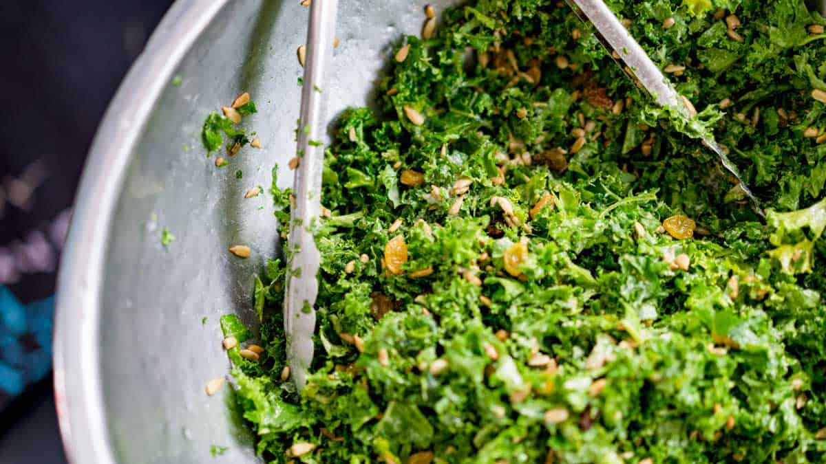 Close up of green salad being tossed with tongs.