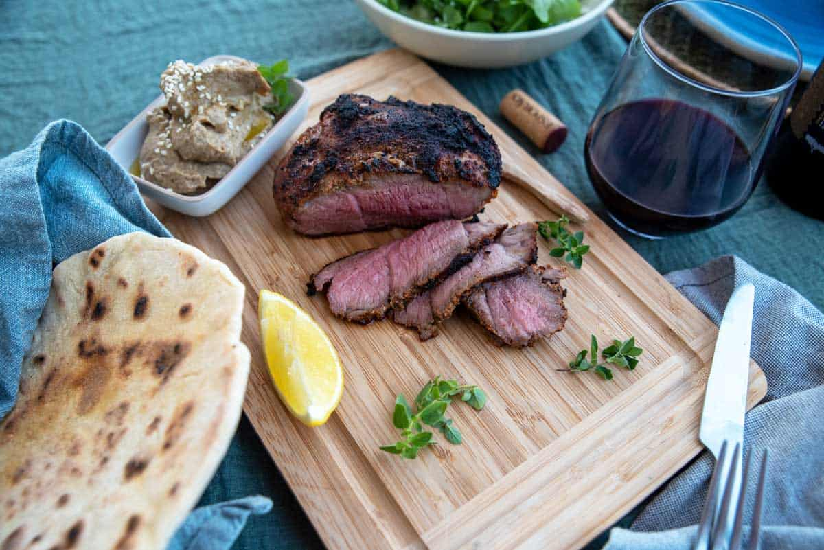 Roasted lamb slices on a board with flat bread, baba ganoush dip and glass of red wine.