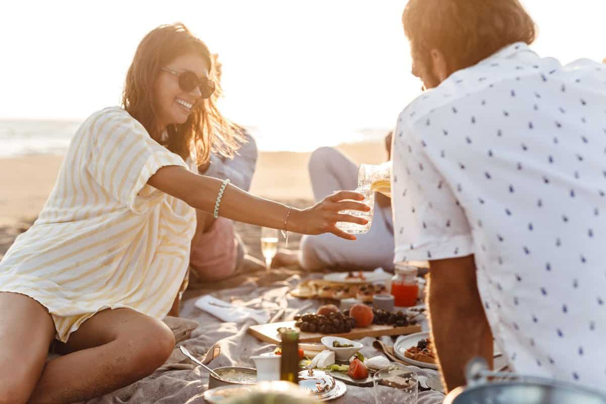 Young couple enjoying a beach picnic with a group of friends.