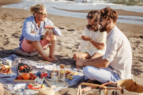 Young people enjoying a picnic on the beach.