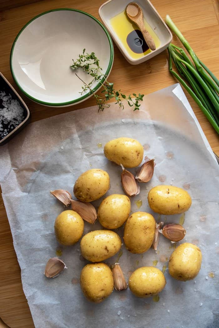 Preparing potatoes and garlic fro roasting with oil and salt.