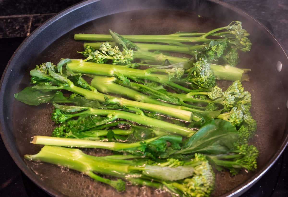 Par boiling Broccoli  in pan of water.