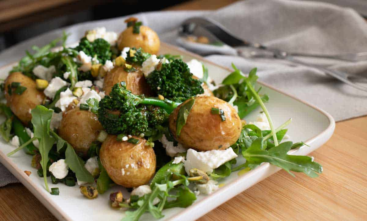 Plate of roast potato salad with broccolini and feta.