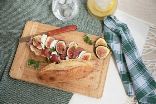 Fig and prosciutto baguette on a picnic blanket.