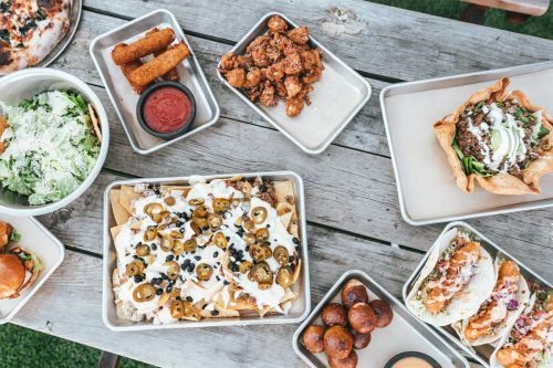 Assorted hot food laid out on a picnic table.