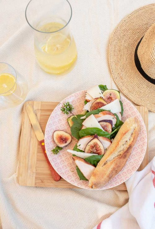 Fig and chicken baguette on a picnic blanket next to a straw hat.