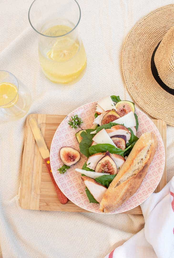 Picnic scene with summer hat, lemon water and chicken and fig baguette.