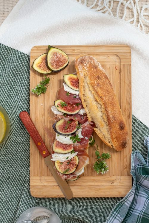 Fig and prosciutto baguette sandwich on a wooden board.