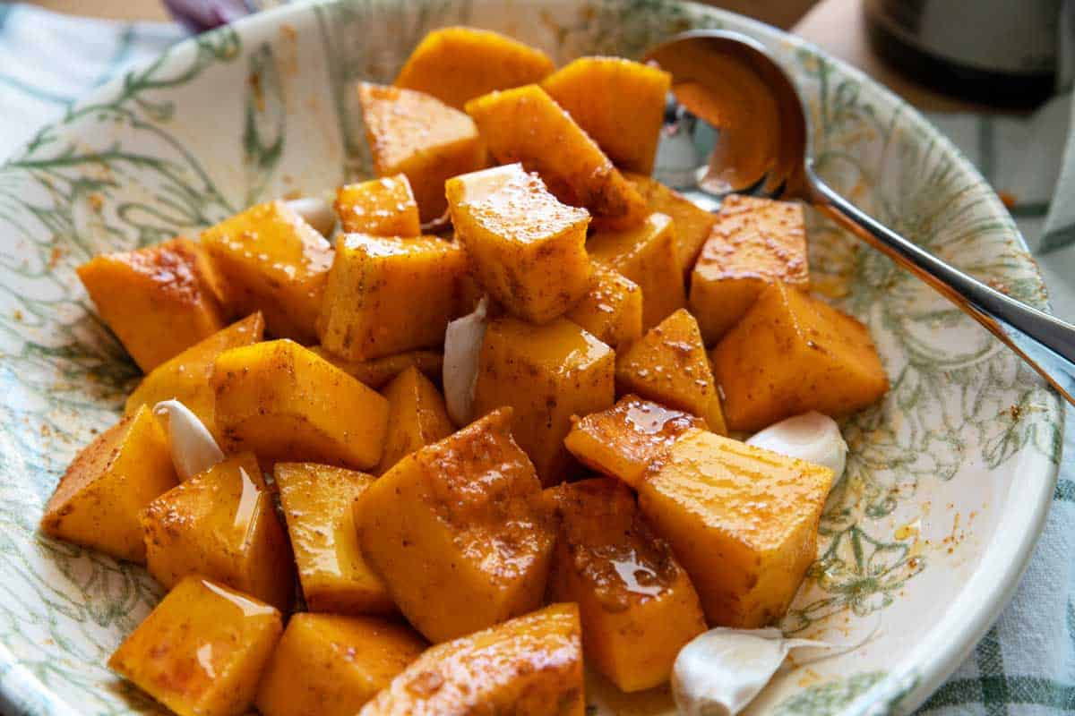 Bowl of pumpkin cubes with spices and olive oil.