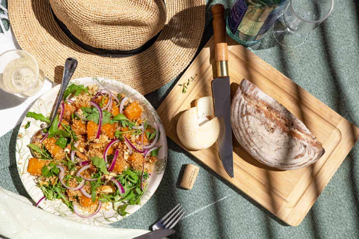 Picnic scene with pumpkin salad, fresh bread and cheese and a straw hat.