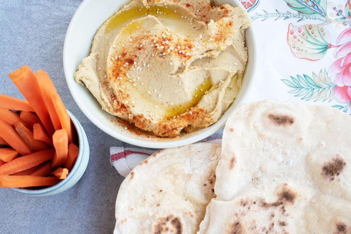 Bowl of hummus with flat bread and carrot sticks.