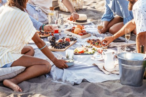 Group of people enjoying a beach picnic with lots of food laid out on a picnic blanket.