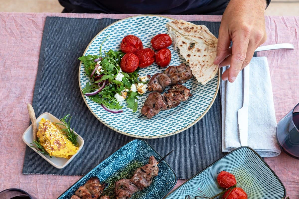 Spiced lamb kebabs with roasted vine tomatoes, flat bread, and pumpkin hummus.