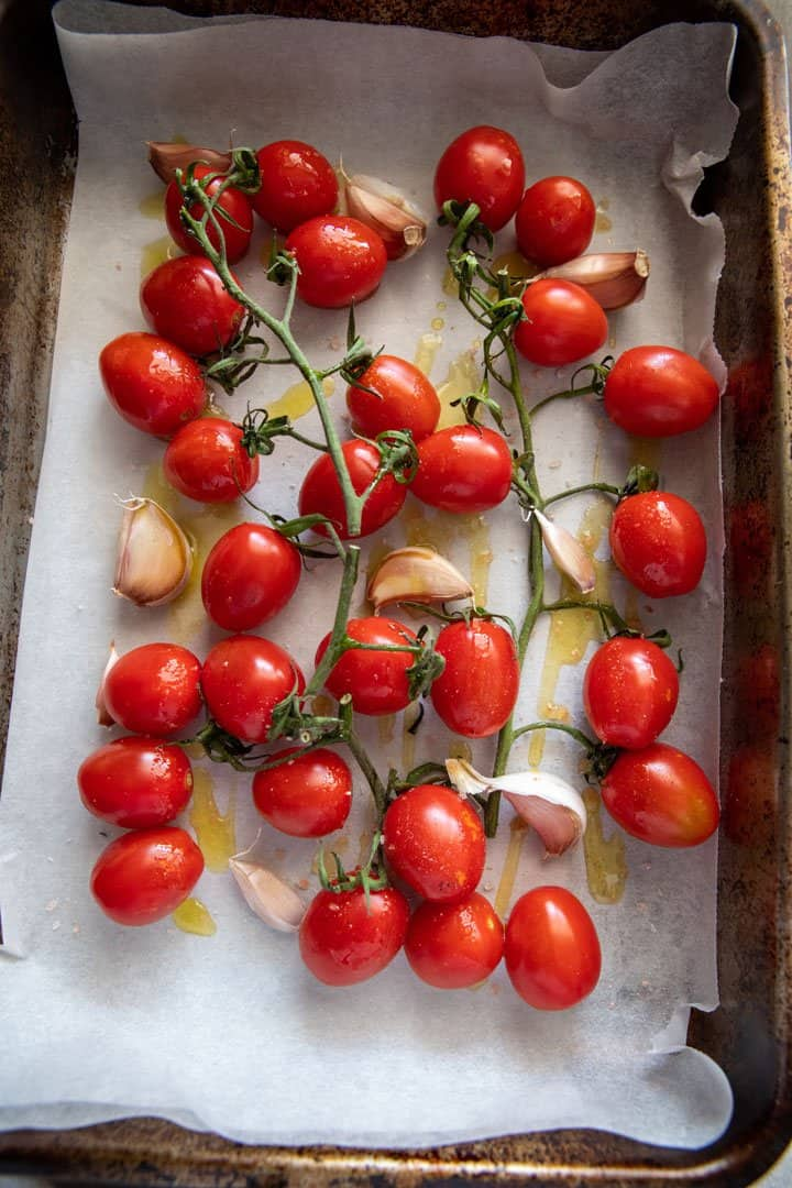 Vine tomatoes in a tray ready for roasting.