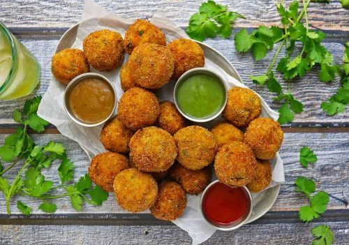 A plate of spicy carrot and spinach croquettes with colourful dipping sauces.