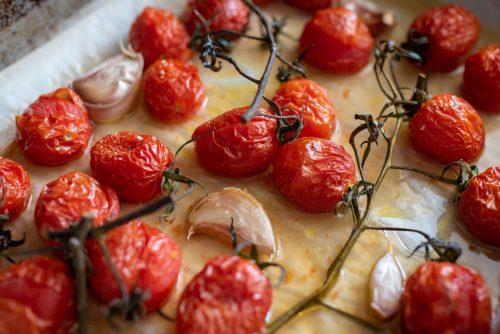 Baking sheet of slow roasted vine tomatoes with cloves of roast garlic.