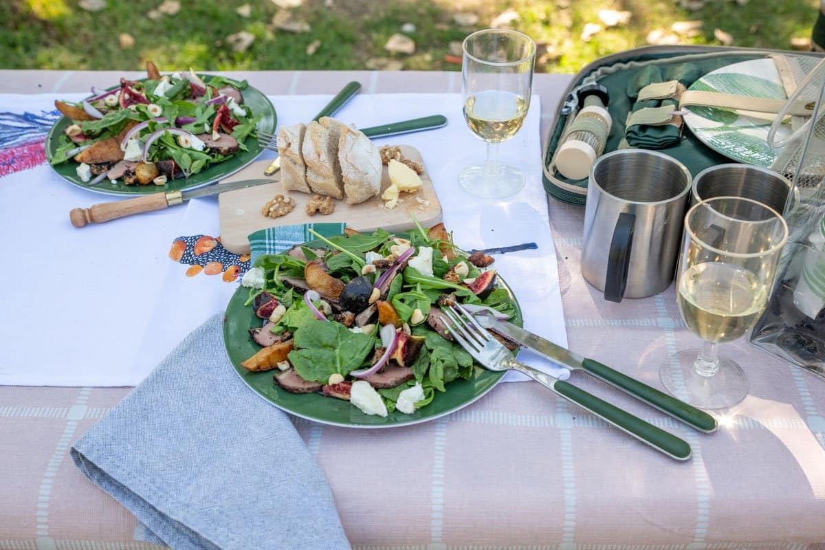 Picnic lunch with duck and grilled pear salad and picnic accessories on the table.