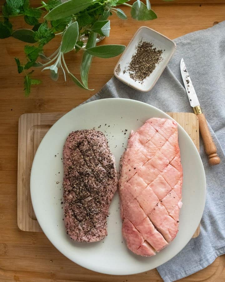 Two raw duck breasts scored for fat rendering, one with cracked pepper.