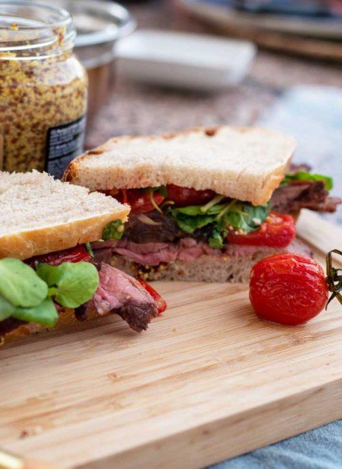 Roast beef sandwich cut in half on a wooden board.