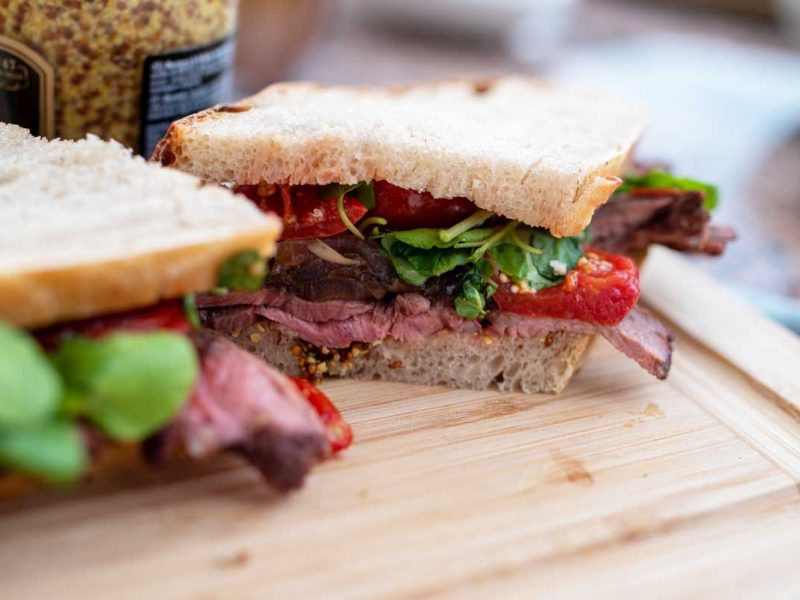 Roast beef sandwich cut in half with slow roasted tomatoes.