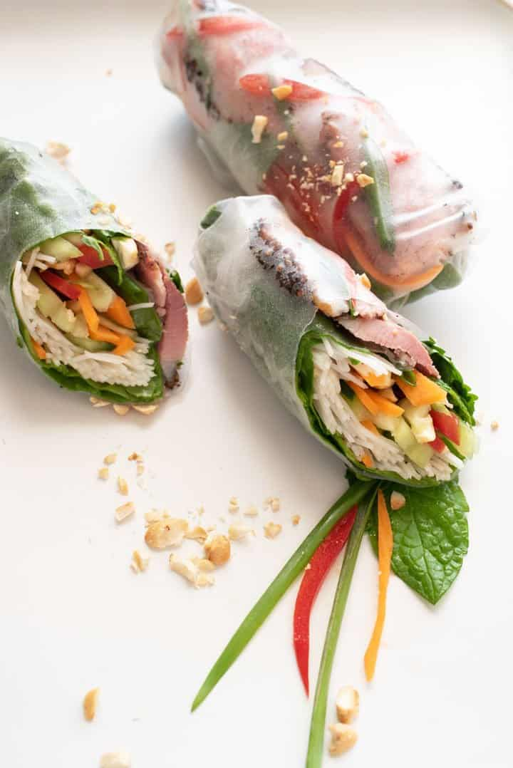 Smoked duck rice paper rolls cut on the angle with ingredients revealed.