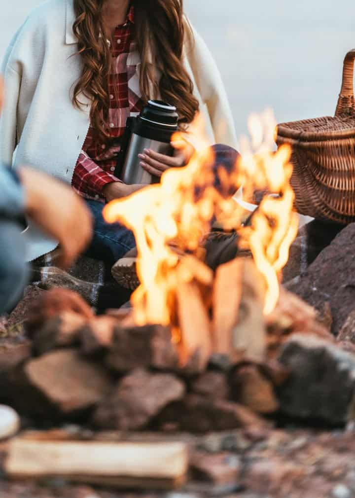 Lady sitting in front of bonfire with picnic basket holding a thermos.