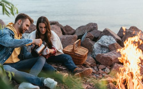 Couple enjoing a winter picnic in front of a bonfire.