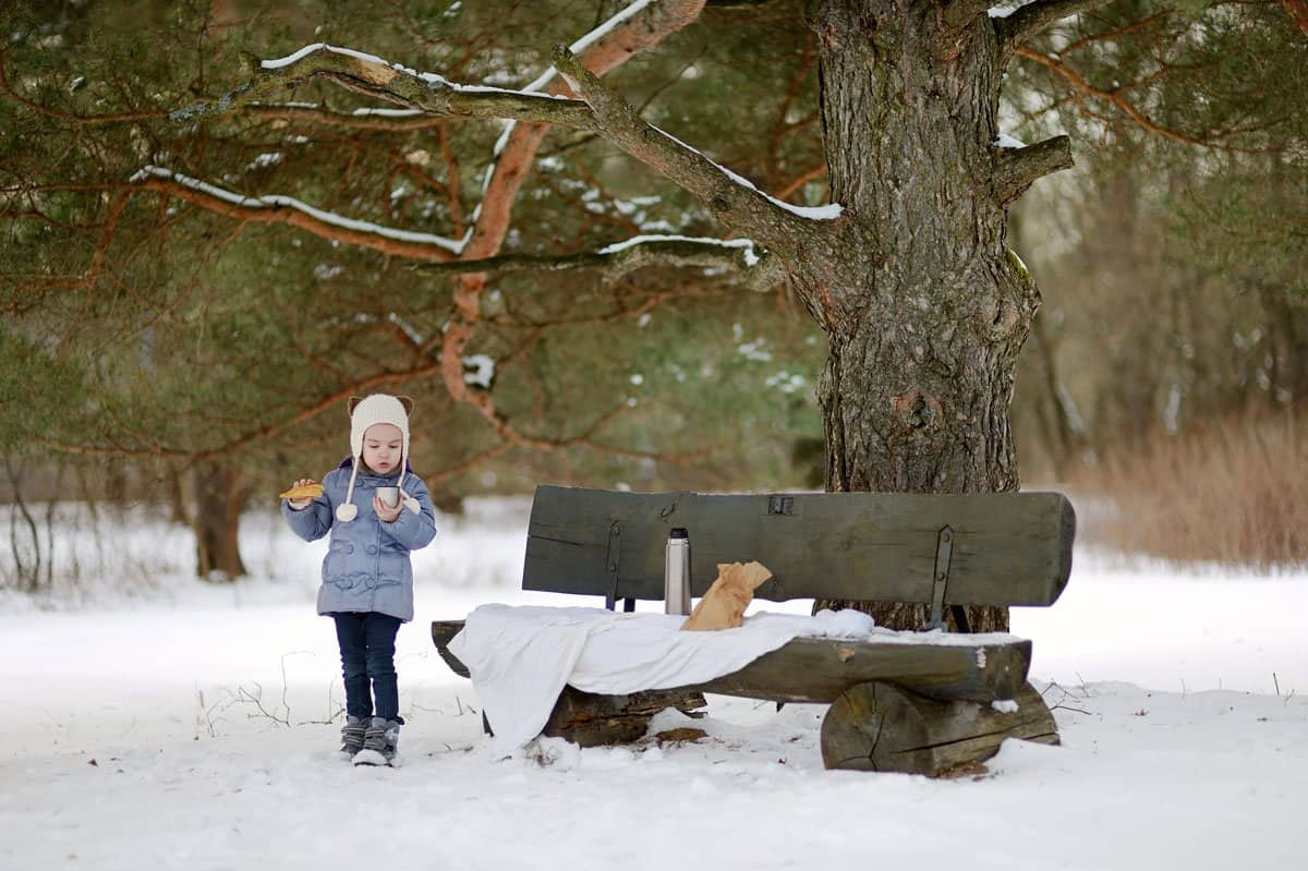 Young girl having a picnic lunch in the snow.