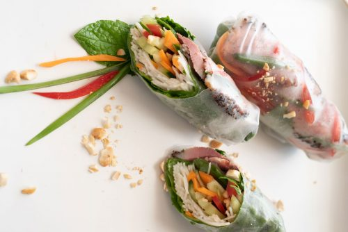Smoked duck rice paper rolls on a white plate.