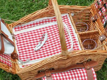 traditional brown wicker picnic basket on green grass with rolled red check blanket and matching insulated insert.