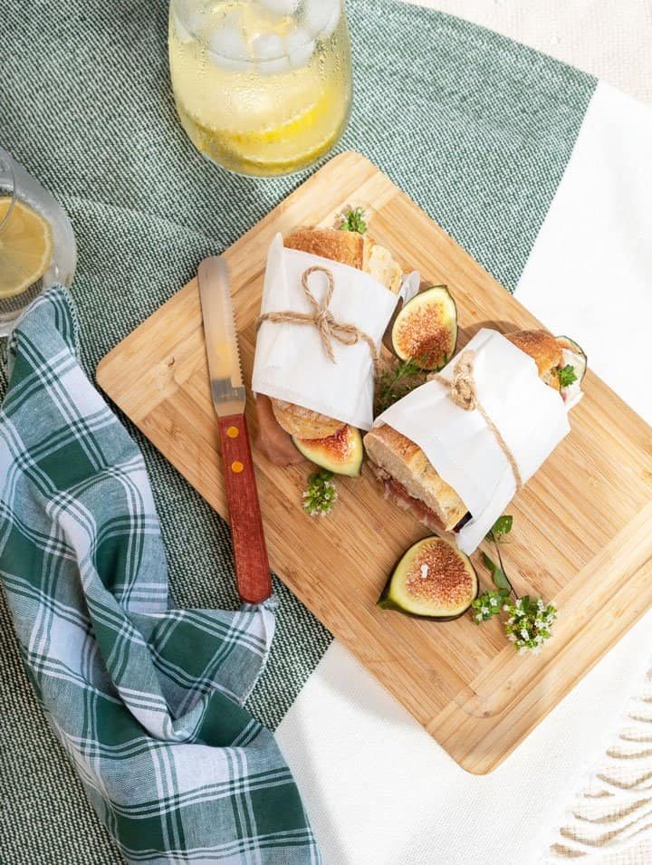 Baguette sandwich halves wrapped in paper and tied with string on a wooden board on a picnic blanket.