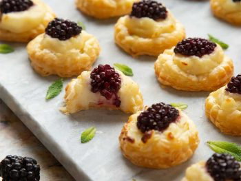Plate of blackberry tartlets with sprigs of mint.
