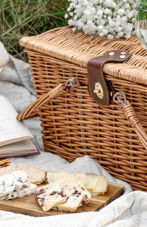 Wicker picninc basket with cheese platter in front.
