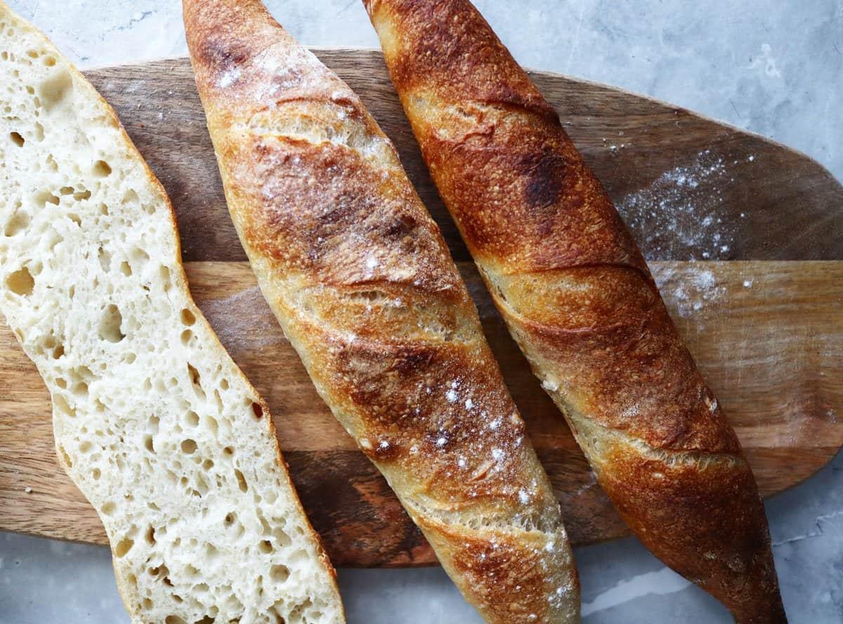 Sourdough baguettes on a bread board.